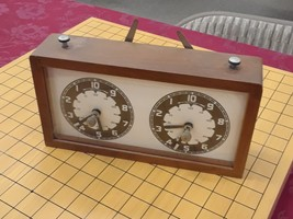 Front face of old mechanical dual clock used for time limits in board games.